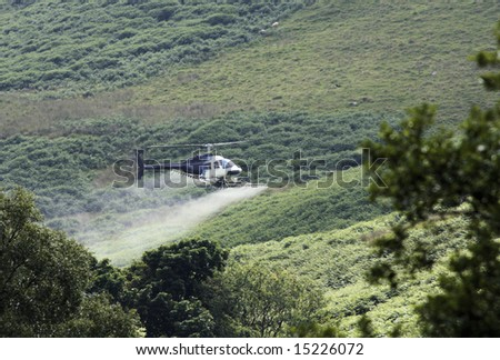 Crop sprayer duster helicopter, spraying mountains, fields and land - stock photo