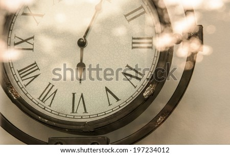 crop steel Vintage analog clock and bright flare reflexing in the mirror sepia  - stock photo
