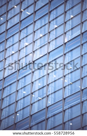 Crop textured background of glass surface with windows of skyscraper.