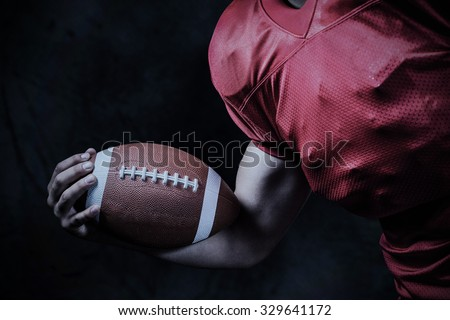 Cropped American football player holding ball against grey background - stock photo
