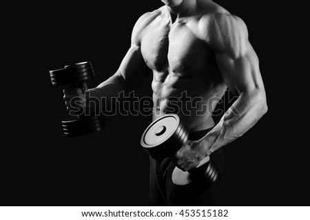 Cropped black and white shot of a muscular male bodybuilder with perfect abs exercising with weights - stock photo