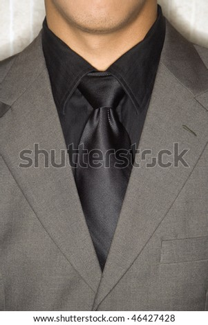 Cropped close-up of businessman's suit jacket and necktie. Vertical format. - stock photo