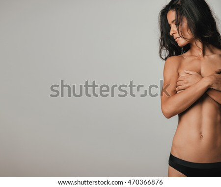 Cropped front view of partially nude fit woman with long black hair and serious expression looking sideways while covering her chest. Copy space over gray background