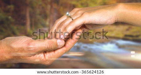 Cropped hand of couple holding hands against autumn scene