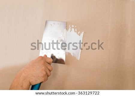 Cropped hand of man using putty knife on brown wall at home - stock photo