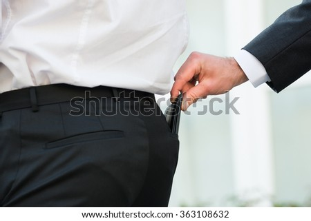 Cropped hand pickpocketing wallet of businessman outdoors - stock photo