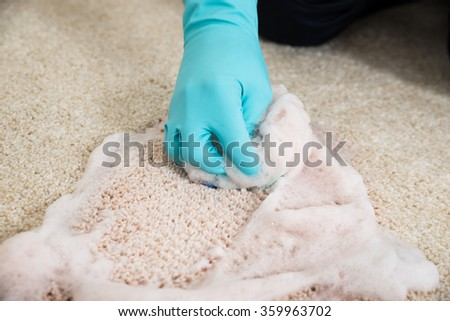 Cropped hands cleaning rug with foam at home - stock photo