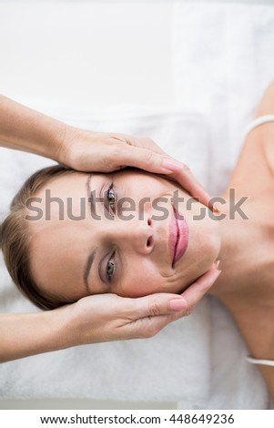 Cropped hands of masseur massages woman at spa