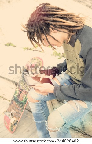 Cropped image male freelancer with dreadlocks sitting with digital tablet typing message warm filter applied - stock photo