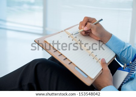 Cropped image of a businessman making his day timetable on the foreground - stock photo