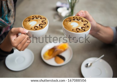 Cropped image of a couple drinking latte coffee in the coffee shop on the foreground  - stock photo