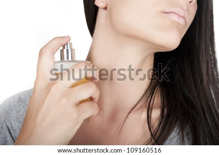 Cropped image of a cute young woman with a perfume bottle in her hand. - stock photo