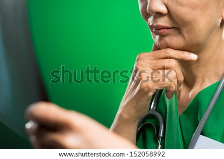 Cropped image of a female doctor in deep contemplation on the foreground  - stock photo