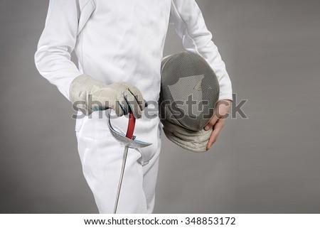 Cropped image of a foil fencer on gray background with space for your text.  - stock photo