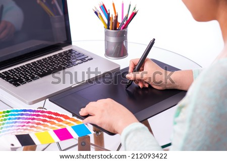Cropped image of a graphic designer using graphic tablet in her work on the foreground.  A concept of digital working. Modern workplace office  - stock photo