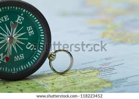 Cropped image of a green vintage compass on the top of a map - stock photo