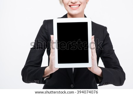 Cropped image of a happy businesswoman showing blank tablet computer screen isolated on a white background - stock photo