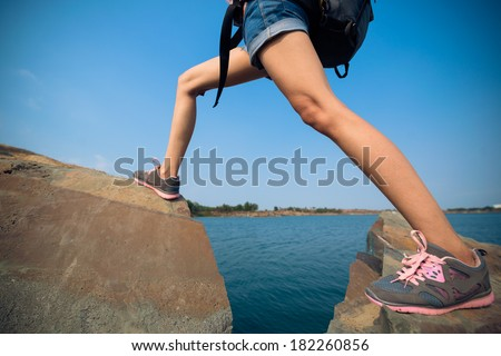 Cropped image of a hiker extremely standing on the rocks  - stock photo