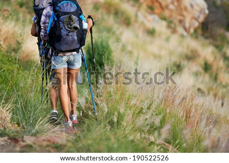 Cropped image of a hiking couple walking along a hiking trail - stock photo