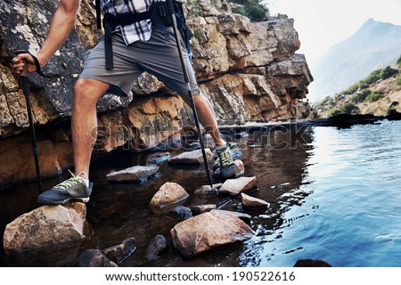 Cropped image of a man balancing on the rocks in the water he is trying to get across with copyspace - stock photo