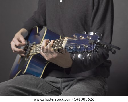 Cropped image of a man strumming acoustic guitar while sitting on a dark background - stock photo