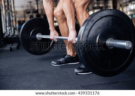 Cropped image of a muscular fitness healthy man lifting heavy barbell at the gym - stock photo
