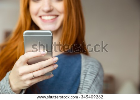 Cropped image of a smiling redhead woman using smartphone - stock photo