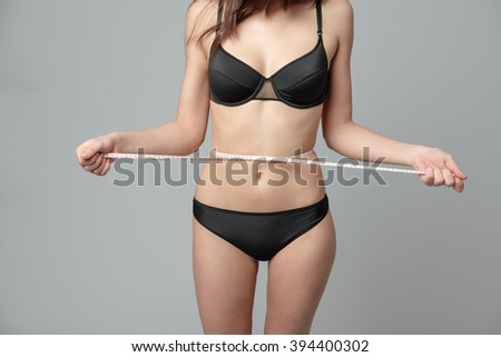 Cropped image of a woman with measuring tape on gray background - stock photo