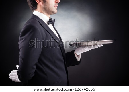 Cropped image of a young waiter holding an empty dish on black background - stock photo