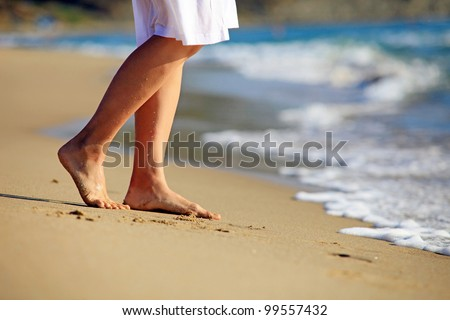 Cropped image of a young woman walking on a beach - stock photo