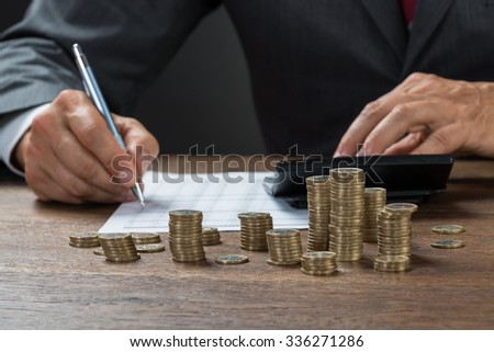 Cropped image of accountant calculating profit with coins on desk - stock photo