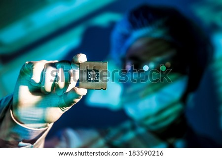 Cropped image of an engineer holding computer microchip on the foreground  - stock photo