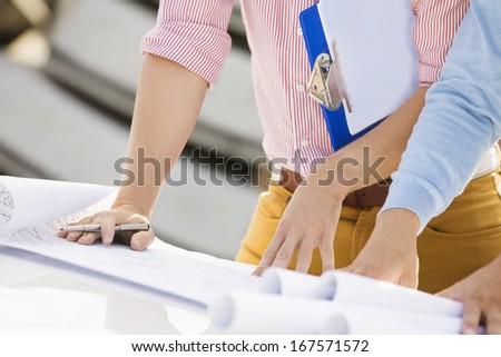 Cropped image of architects with blueprints and clipboard - stock photo
