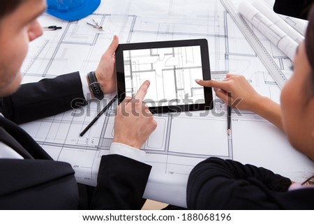 Cropped image of architects with digital tablet working on blueprint at desk in office - stock photo