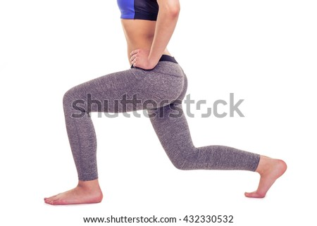 Cropped image of attractive young woman in sportswear stretching while doing yoga, isolated on white background - stock photo