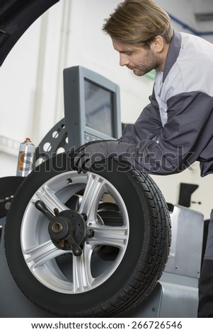 Cropped image of automobile mechanic repairing car's wheel in workshop - stock photo