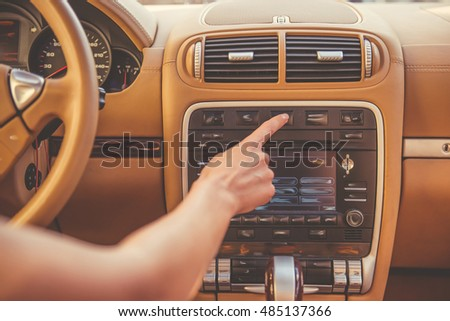 Cropped image of beautiful young woman pressing button on the panel of the car while driving