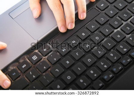 Cropped image of boy's schoolboy's hand typing on laptop keyboard