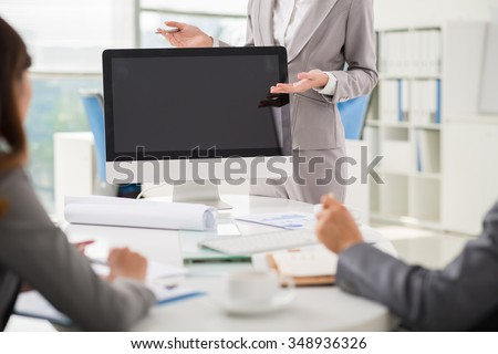 Cropped image of business lady using computer monitor when conducting presentation - stock photo