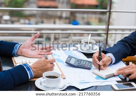 Cropped image of business people analyzing financial documents - stock photo
