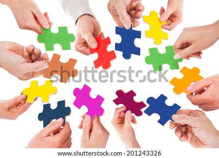 Cropped image of business people holding colorful jigsaw pieces over white background - stock photo