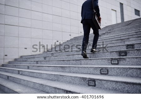 Cropped image of business person going up the stairs - stock photo