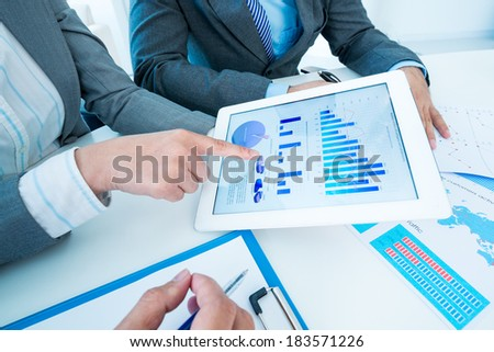 Cropped image of business team pointing at business document in touchpad  - stock photo