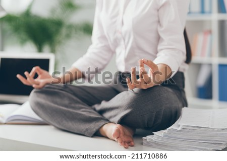 Cropped image of business woman practicing yoga in the office - stock photo