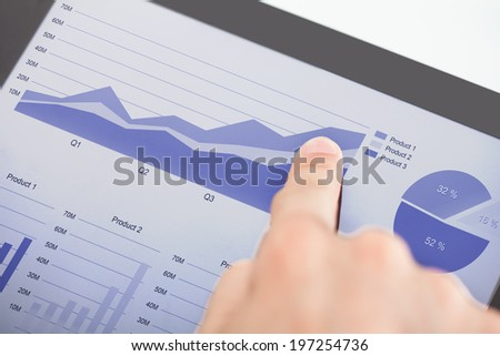 Cropped image of businessman analyzing graphs on digital tablet - stock photo