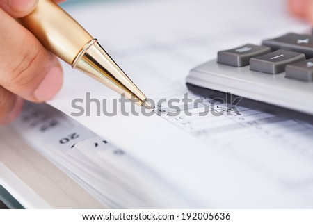 Cropped image of businessman checking expense in office - stock photo