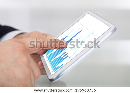 Cropped image of businessman comparing graphs on digital tablet at desk in office - stock photo