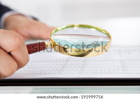 Cropped image of businessman examining audit with magnifying glass at desk in office - stock photo