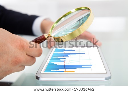 Cropped image of businessman examining graph on digital tablet with magnifying glass at office desk - stock photo