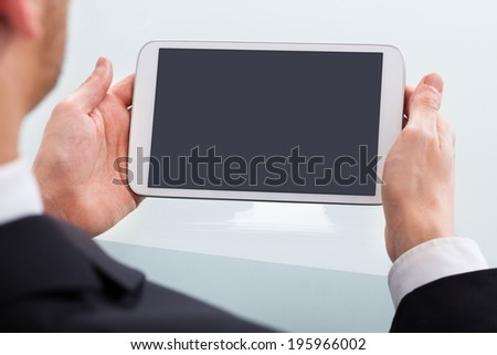 Cropped image of businessman holding digital tablet at desk in office - stock photo